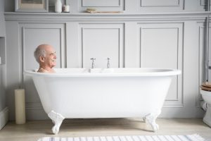 Man in his 70s enjoying a bath, relaxing in a hotel bathroom with a happy contended expression.